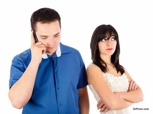 Businessman neglecting his girlfriend while speaking on the phone