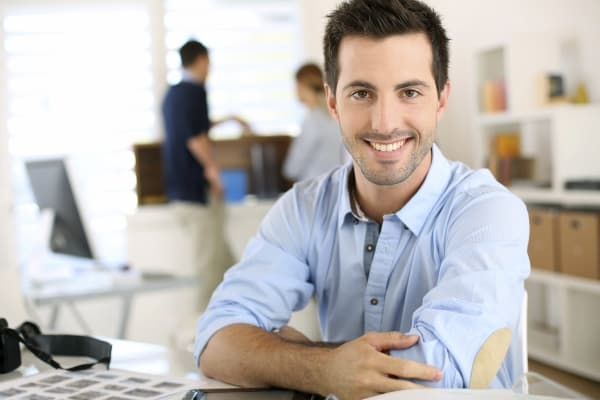 Smiling man with arms crossed in office