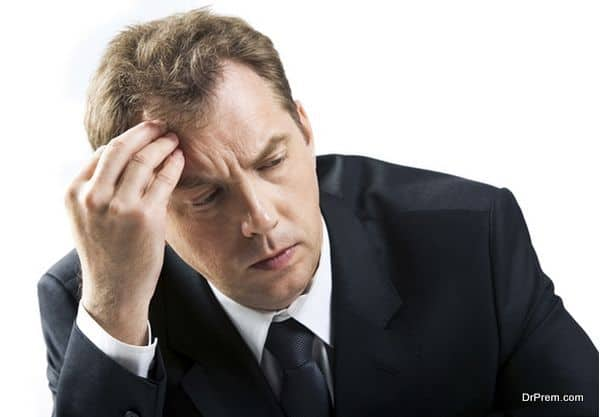 stressed businessman touching his head while thinking
