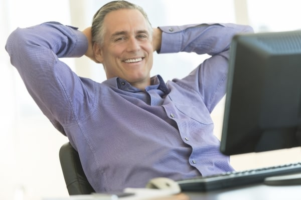 Businessman Sitting With Hands Behind Head At Office Desk