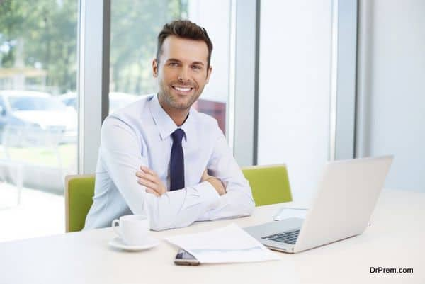 Happy man sitting at desk in the office