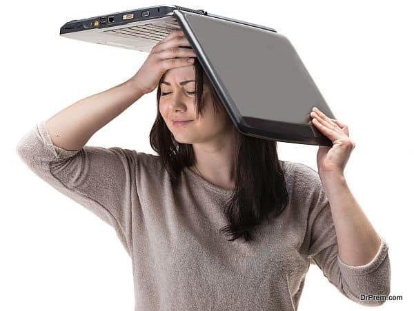 Stressed young woman with a laptop on her head