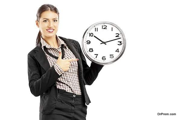 Smiling female standing and pointing on a wall clock