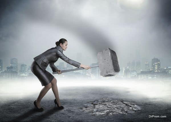Businesswoman with sledgehammer banging the ground