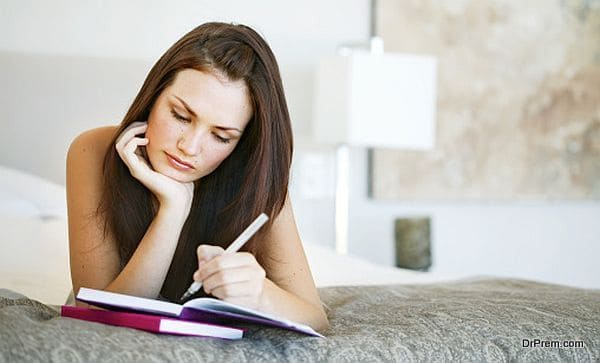 Young woman lying on a bed writing in a notebook