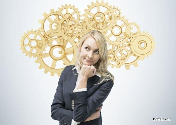 Beautiful blonde business woman is thinking about optimisation of the business process. A concept of business management solutions. Golden gears as a cloud.