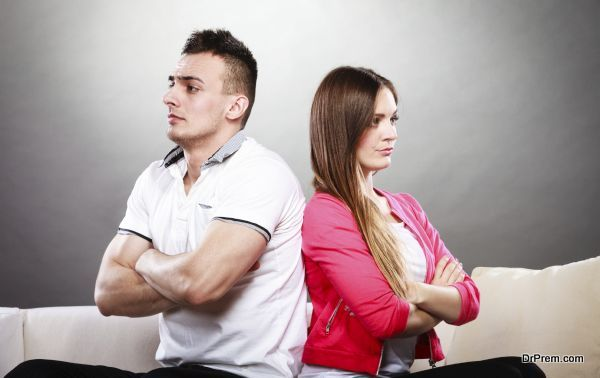 Bad relationship concept. Man and woman in disagreement. Young couple after quarrel sitting on sofa back to back