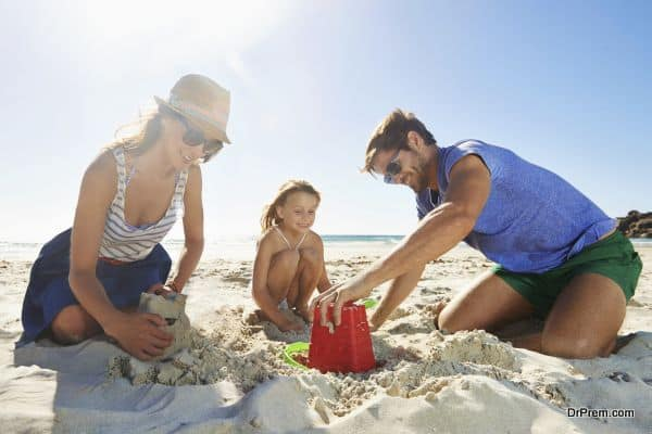 Shot of a young family building a sandcastle on a beach