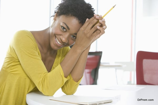 Businesswoman With Notepad And Pencil Sitting At Table