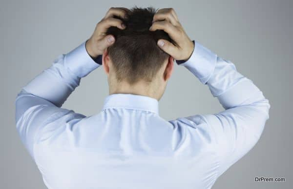 Stressed businessman with headache standing back to camera