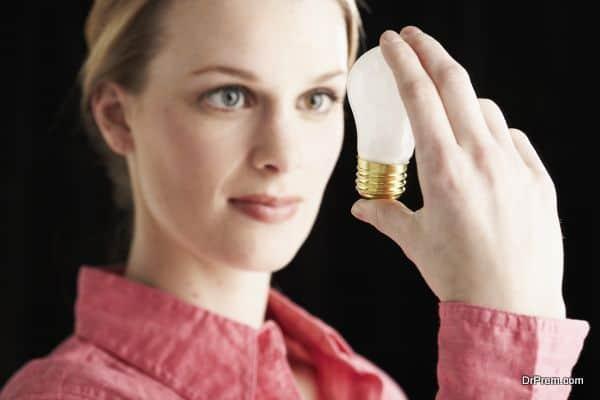 Focused woman looking at lightbulb