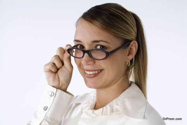 Blonde woman with hands on glasses, close-up