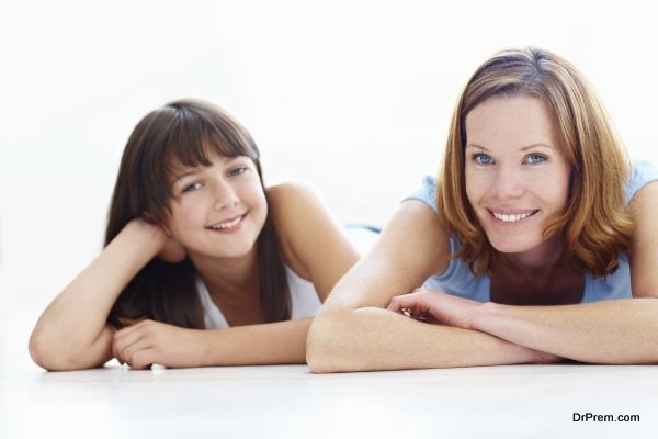 Portrait of happy mother and daughter lying on floor smiling on white