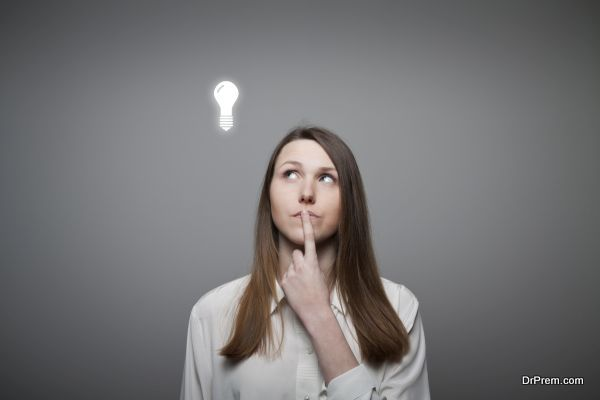 Young woman having an idea with light bulb over her head.