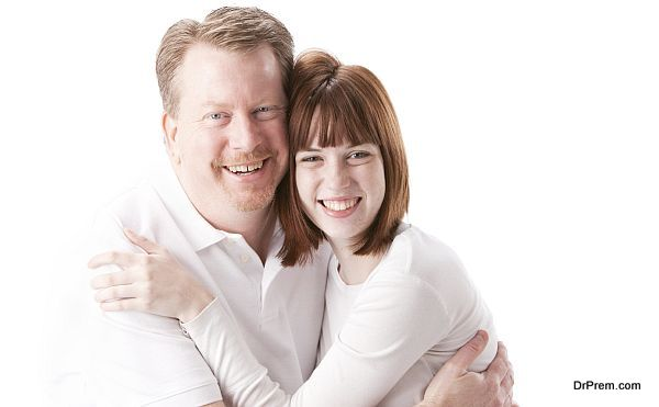 A head and shoulders image of a caucasian real family with a father hugging his teenage daughter. Marty and Anna Cline
