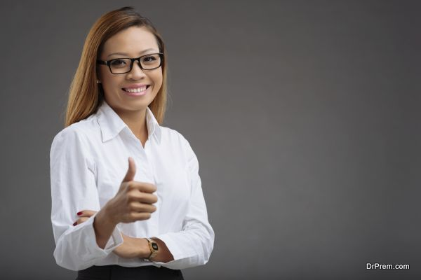 Portrait of smiling Asian business woman showing thumbs-up