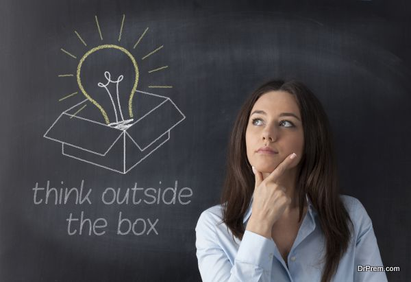 Businesswoman standing in front of chalkboard with light bulb and box drawn above her head. Concept about ideas
