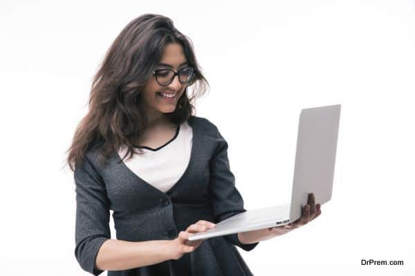 Smiling businesswoman in glasses using laptop isolated on a white background