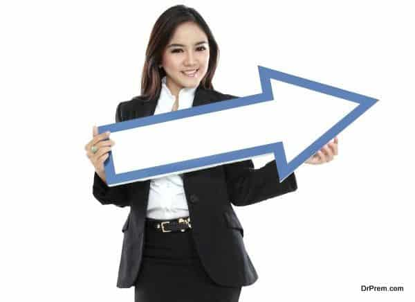 smiling businesswoman with direction arrow sign on white background