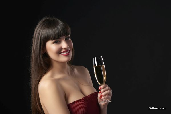 Sensual smiling woman holding a glass with champagne. Closeup portrait with copy space