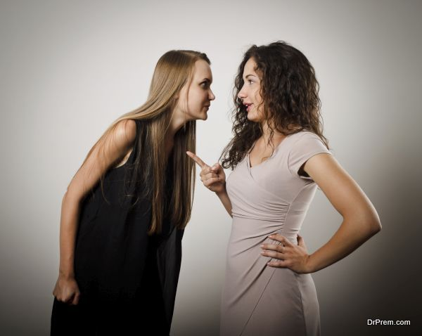 Two young women are arguing about something. Young women are doing something.