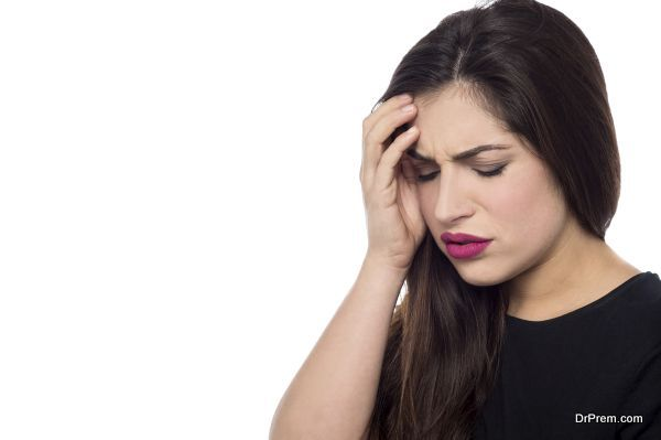 Worried young woman touching her forehead
