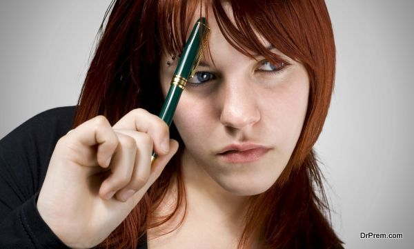 Cute girl with red hair holding a pen against her forehead and thinking.Studio shot.