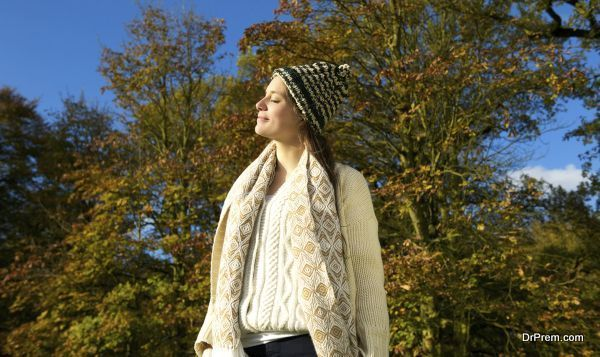 Portrait of an attractive woman in sweater and hat enjoying the sun on an autumn calm day