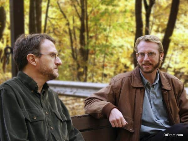 men, coworkers, colleagues, males, friends, pals, buddies, chums, bench park, seated lunch, discussion, serious, smile, trees, autumn, foliage, leaves, yellow, jacket, beard, mustache, glasses, talk, listen, chat, adults, two, nature