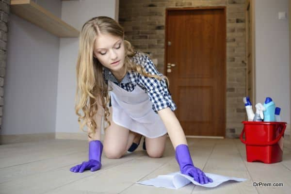 Beautiful young woman washes the floor on her knees. On hands has protective rubber gloves. Behind her, a bucket of cleaning utensils.
