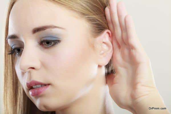 Woman with hand behind ear spying