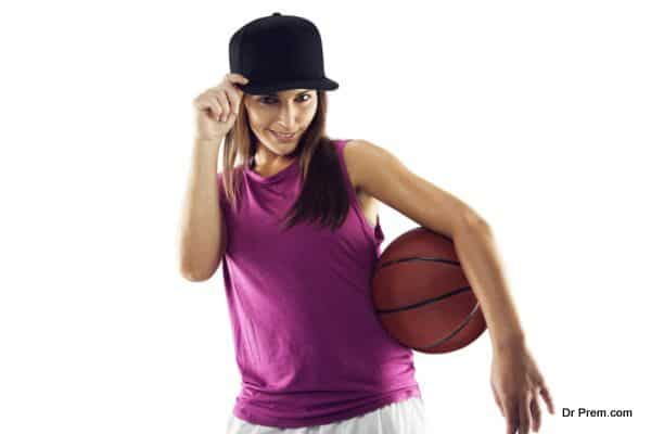 Beautiful and sporty woman holding basketball