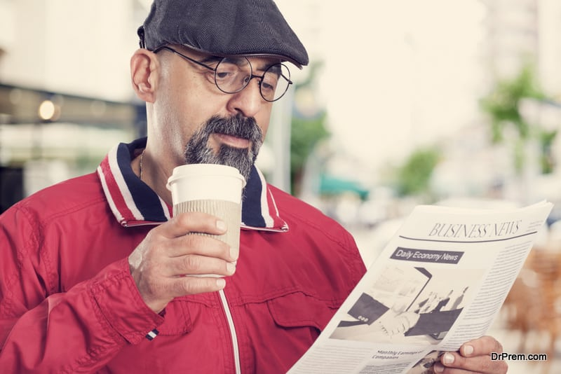 Middle aged man reading newspaper with glasses