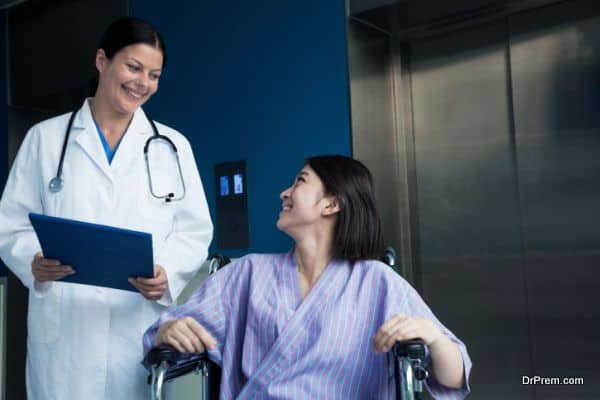 Patient sitting in a wheelchair, looking at doctor beside her