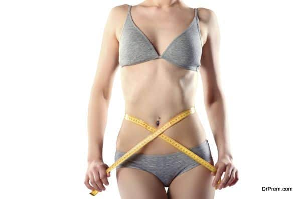 Slim girl with centimeter measuring her slim beautiful body