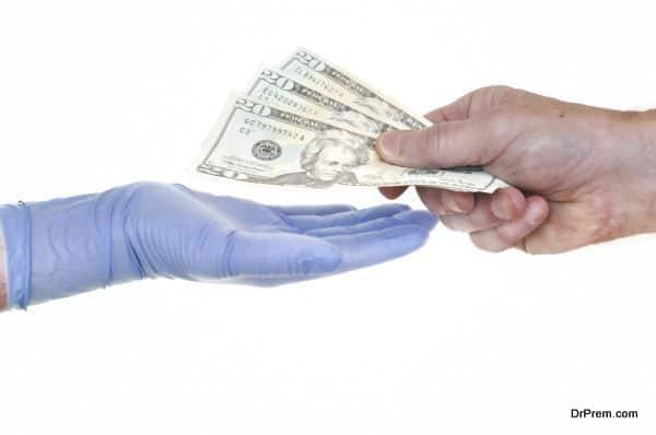 Patient Giving Doctor Money Representing Rising Healthcare Costs