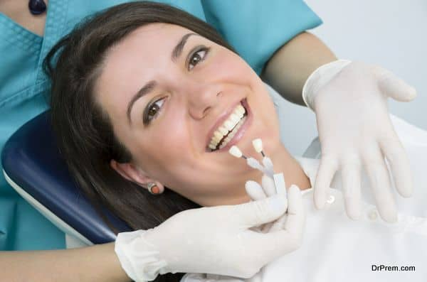 A dentist showing porcelain teeth to pacient