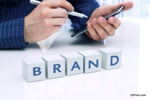 "Businessman arranging small blocks with word ""Brand"""