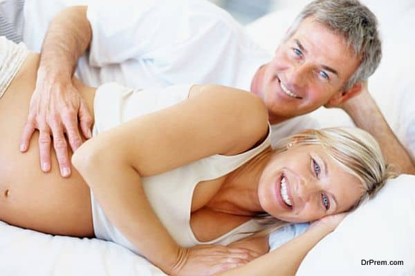 Smiling middle aged pregnant couple lying in bed