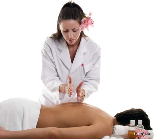 A masseuse performing hacking on a male customers body. Hands can be open or lightly curled into loose fists. Percussive strokes, such as hacking, cupping and plucking, are used to stimulate areas, improve circulation, and release muscle tension.