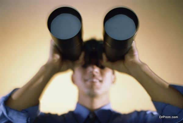 Businessman looking through a pair of binoculars