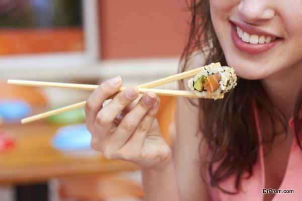 Cropped image of young female eating sushi. Horizontal Shot.