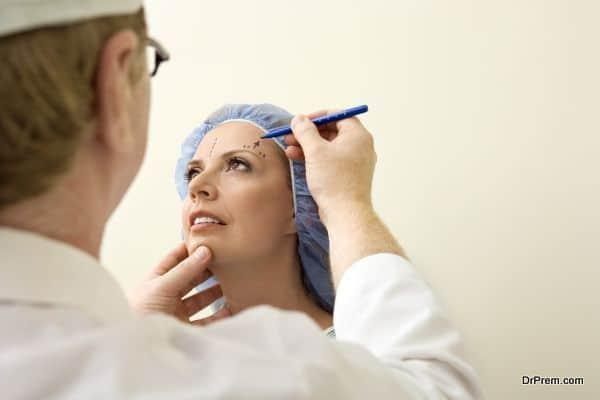 Plastic surgeon marking patient's face
