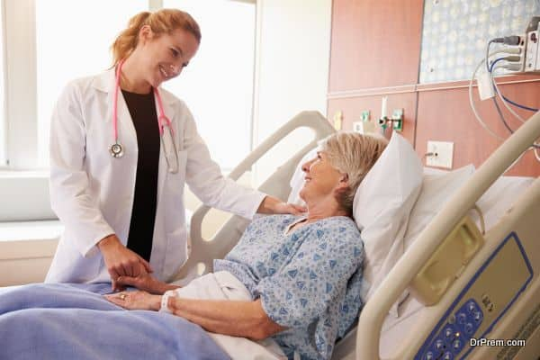 Female Doctor Talks To Senior Female Patient In Hospital Bed