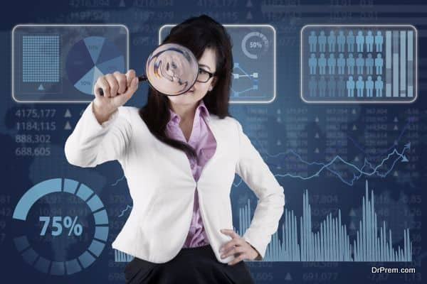 Female entrepreneur using a magnifier to monitoring her business in front of financial background
