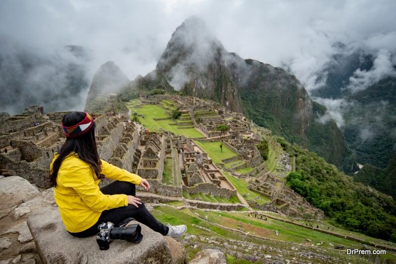 Asian woman traveler looking at Machu Picchu