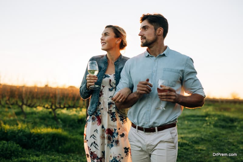 Couple with a glass of wine at vineyard outdoors
