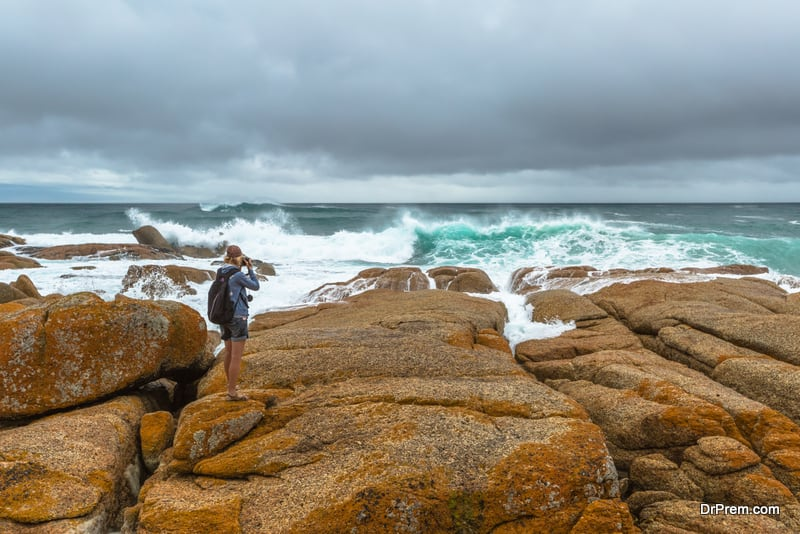 Nature travel photographer woman taking pictures on a cliff in Redbill, famous beach for wind, waves and suf. Tasmania, Australia
