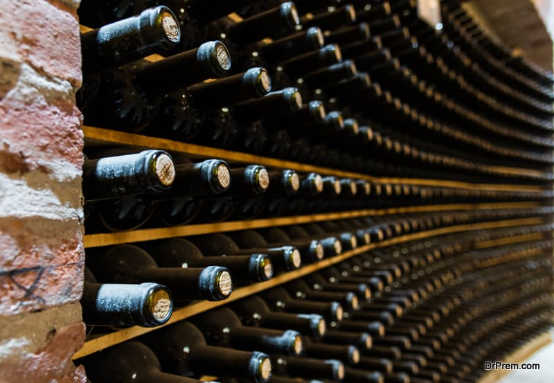 Red wine bottles stored in a wine cellar of a winery
