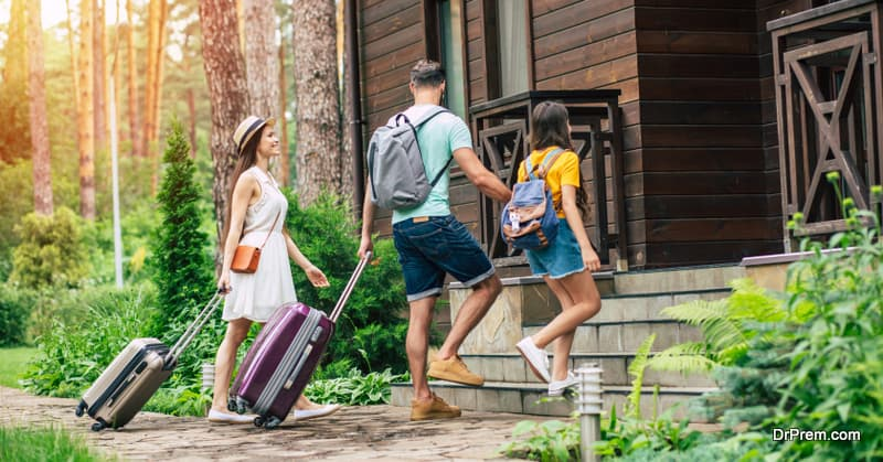 glad family with suitcases and backpacs on a weekend coming to the hotel surrounded by trees